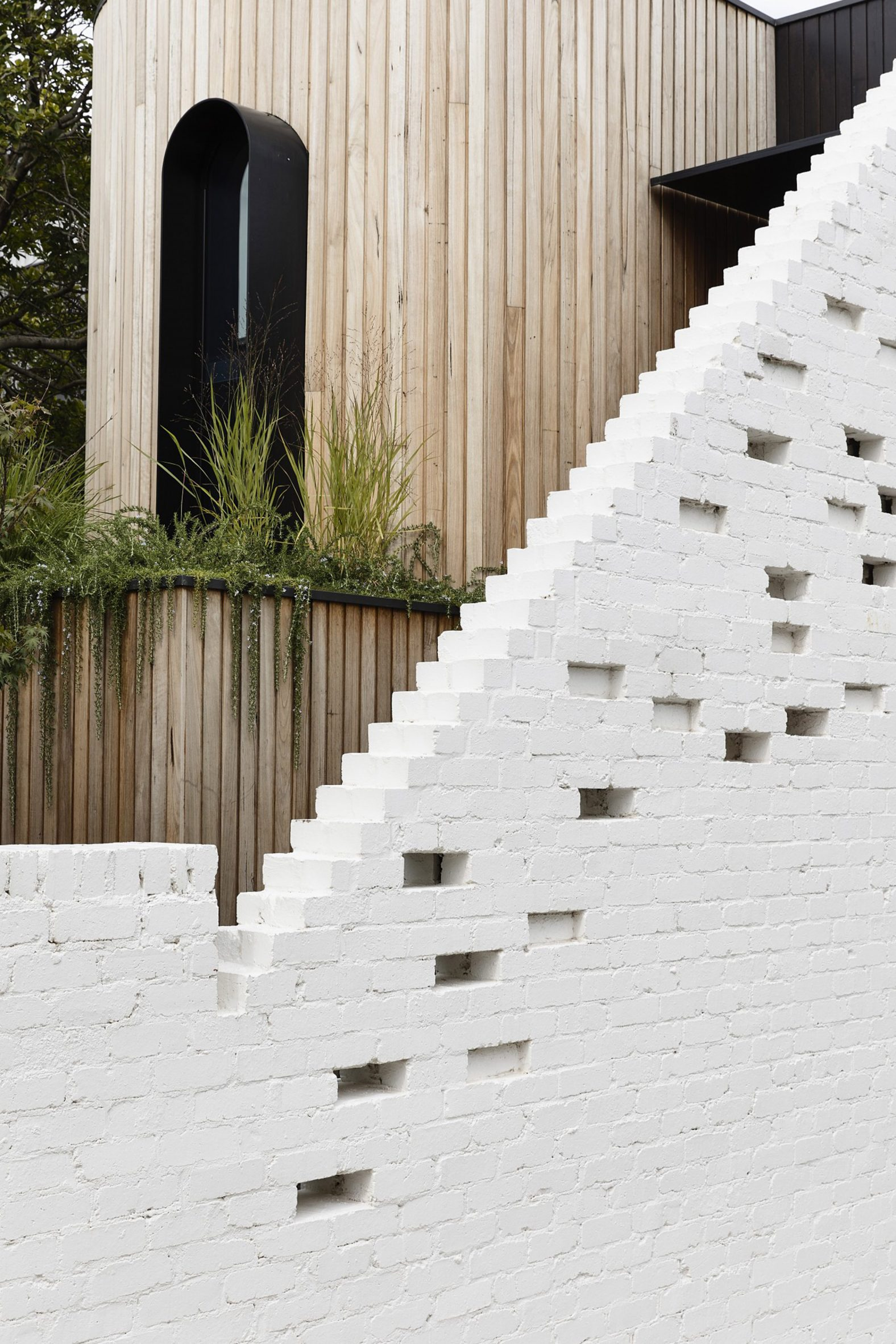 Behind the painted brick wall is a timber structure