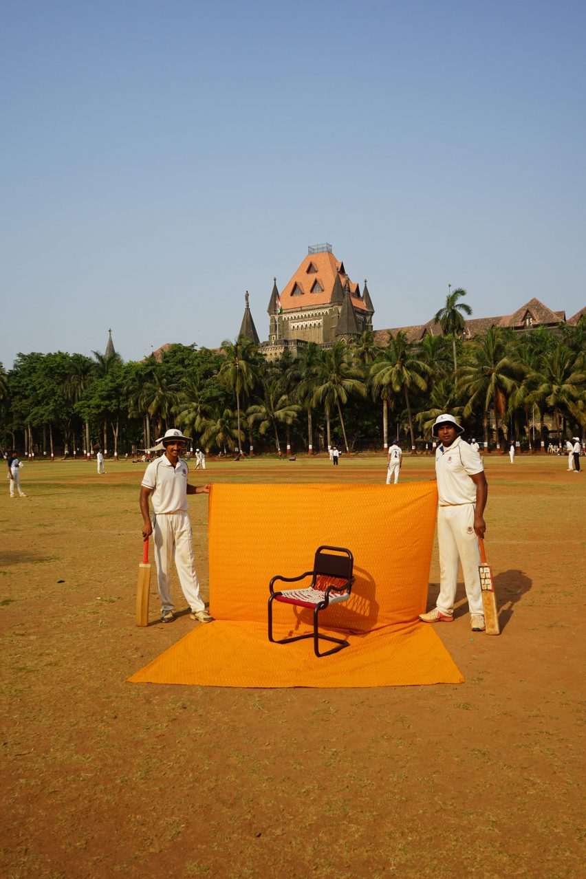Chair photographed against a yellow sheet held by two cricketers on a cricket field in India
