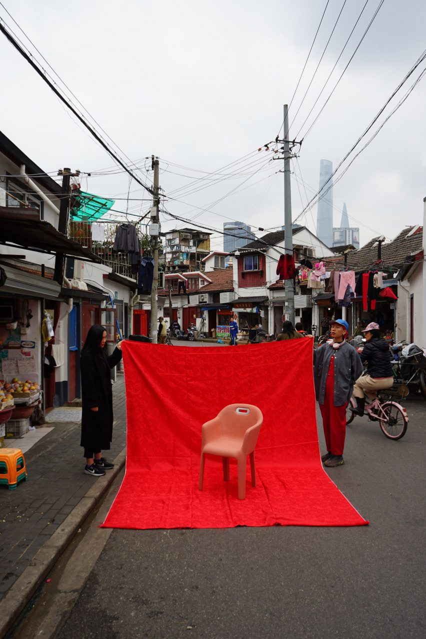 Chair photographed against a red sheet held by two locals on a Chinese street