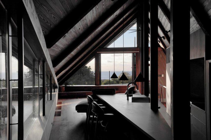 Треугольная барная стойка на кухне переходит в жилое пространство.