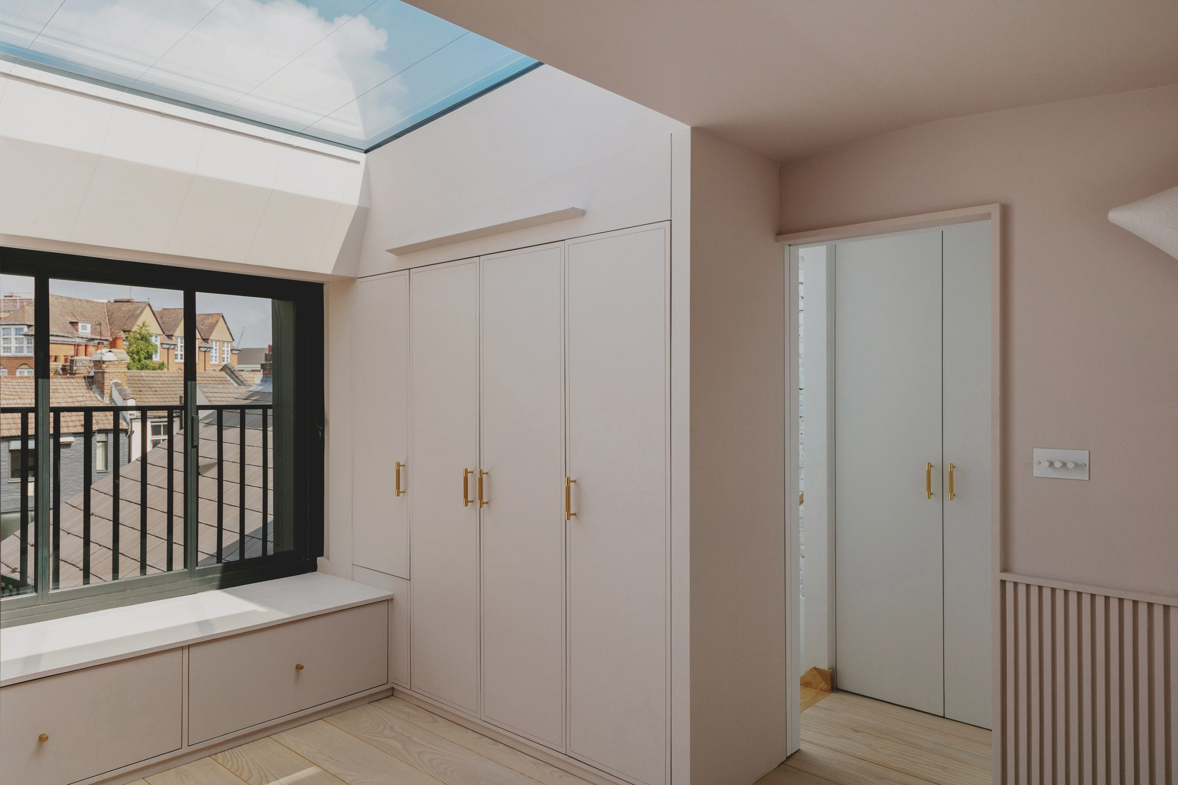 Dressing area in Bed and window in Narford Road loft extension by Emil Eve Architects
