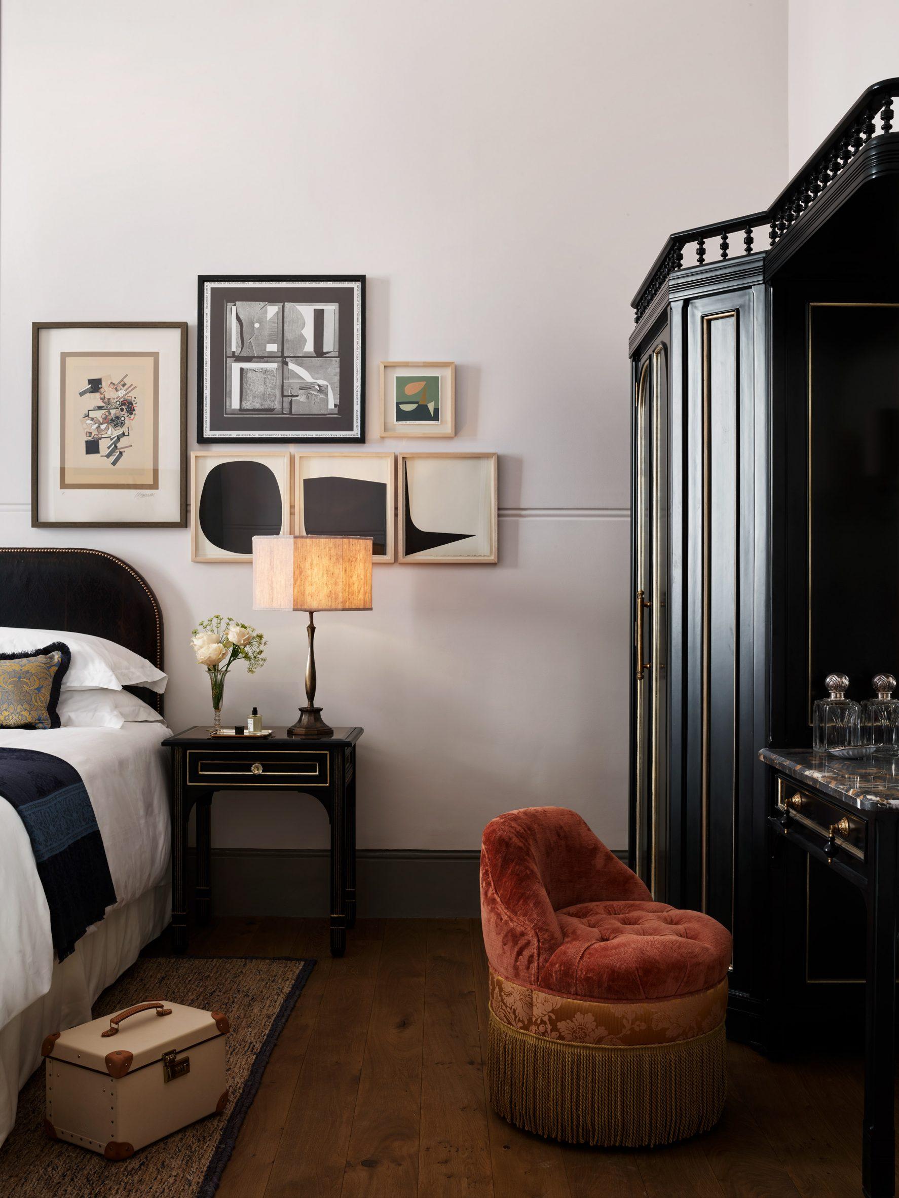 Guest room in NoMad London with tasseled velvet poof