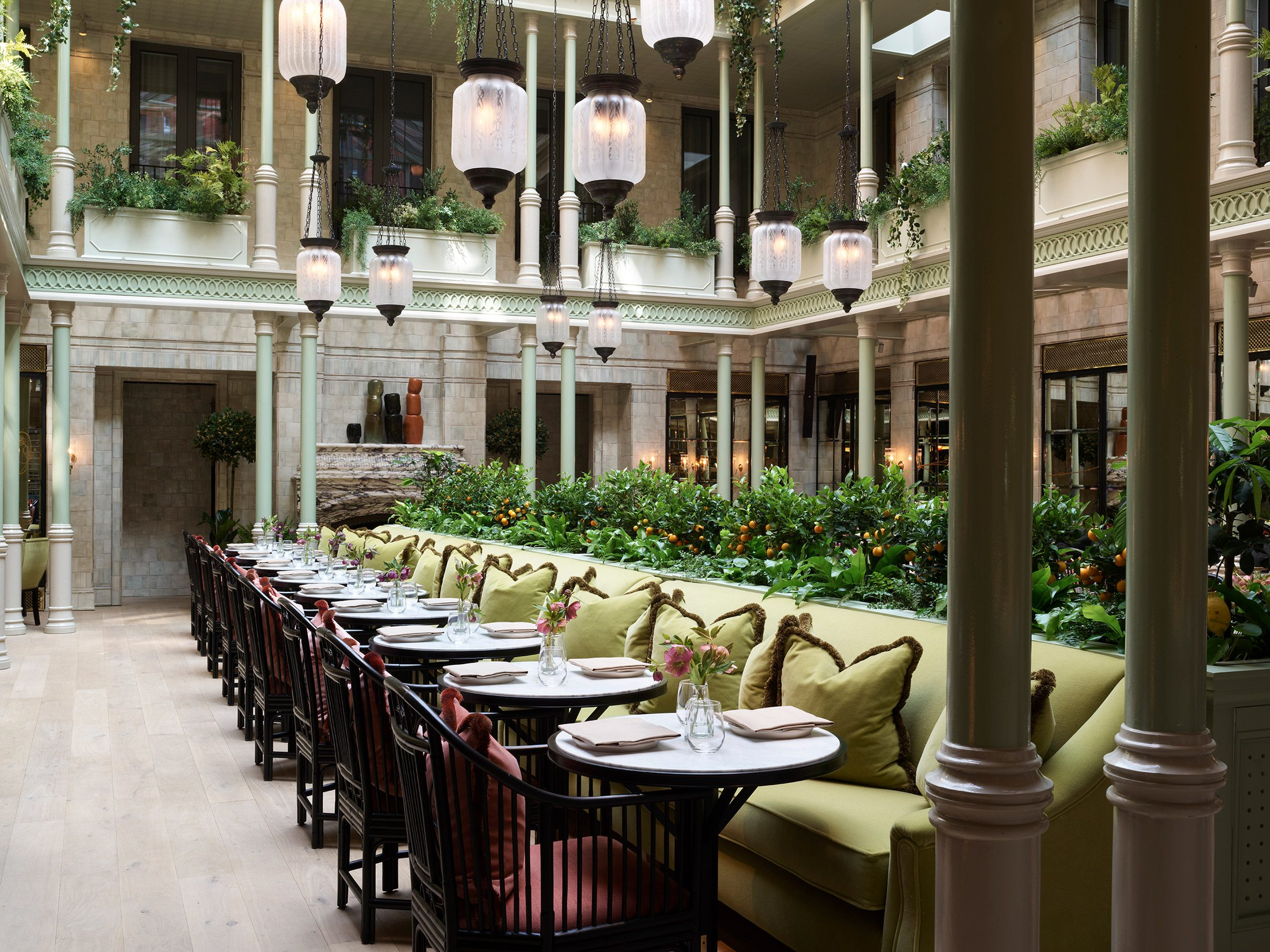 Planting trough and green bench seating in hotel interior by Roman and Williams