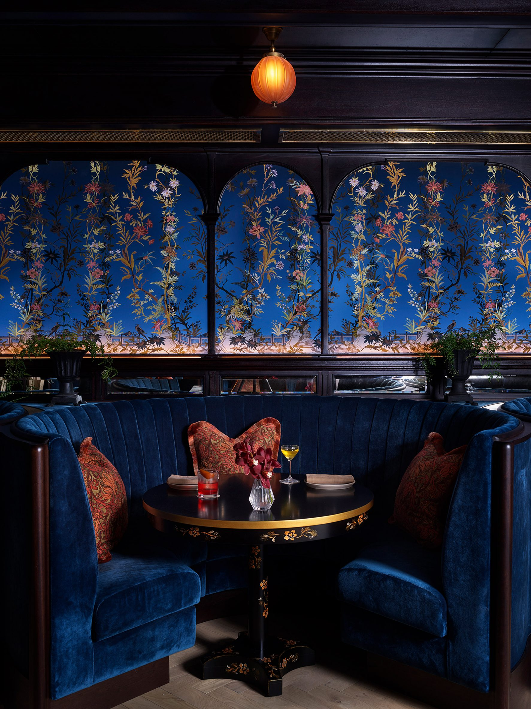 Dining room by Roman and Williams with blue velvet wallpaper