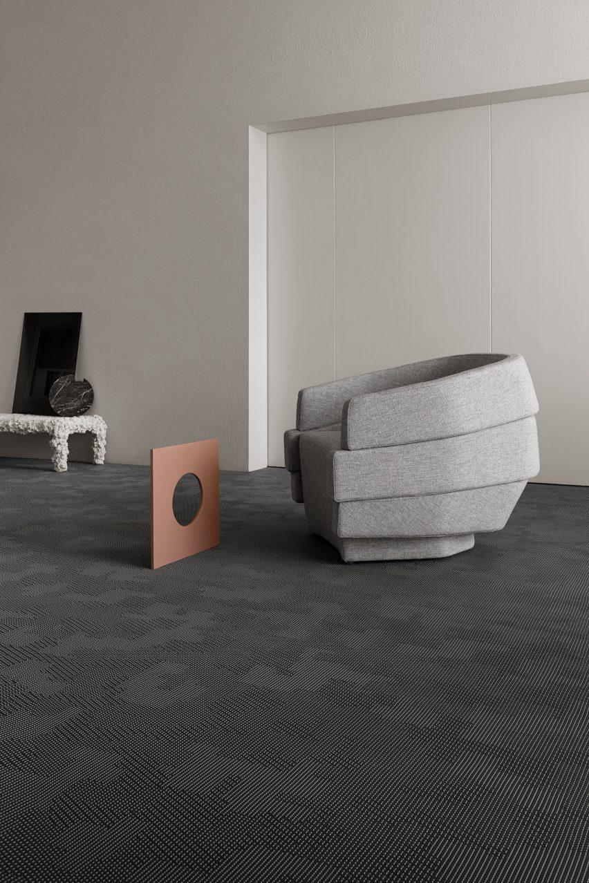 A grey armchair on Bolon by Patricia Urquiola flooring