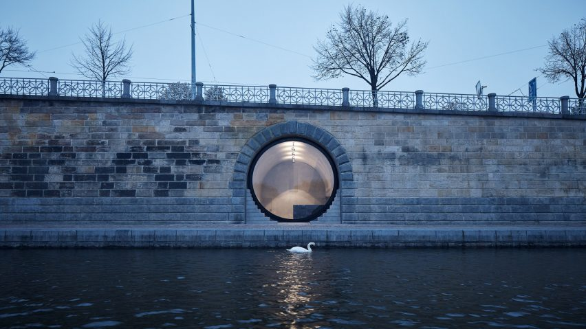 A swan is pictured paddling past a glass fronted vault