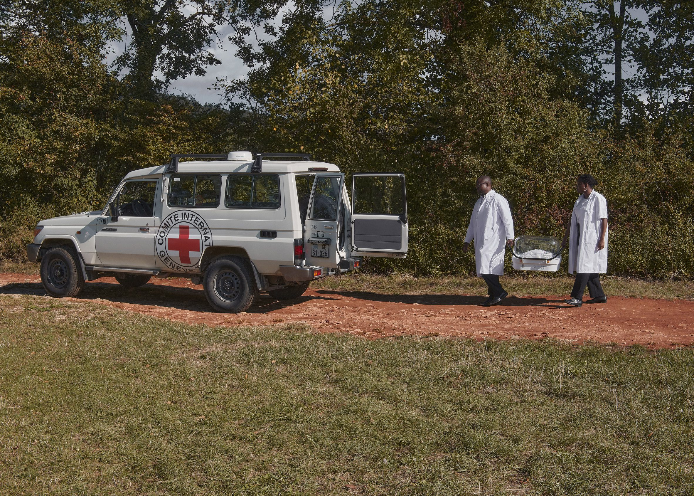 Two medics carry an incubator to an ambulance