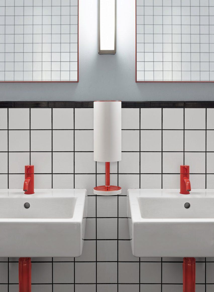 Красно-белый настенный диспенсер RS11 между раковинами в общественном туалете