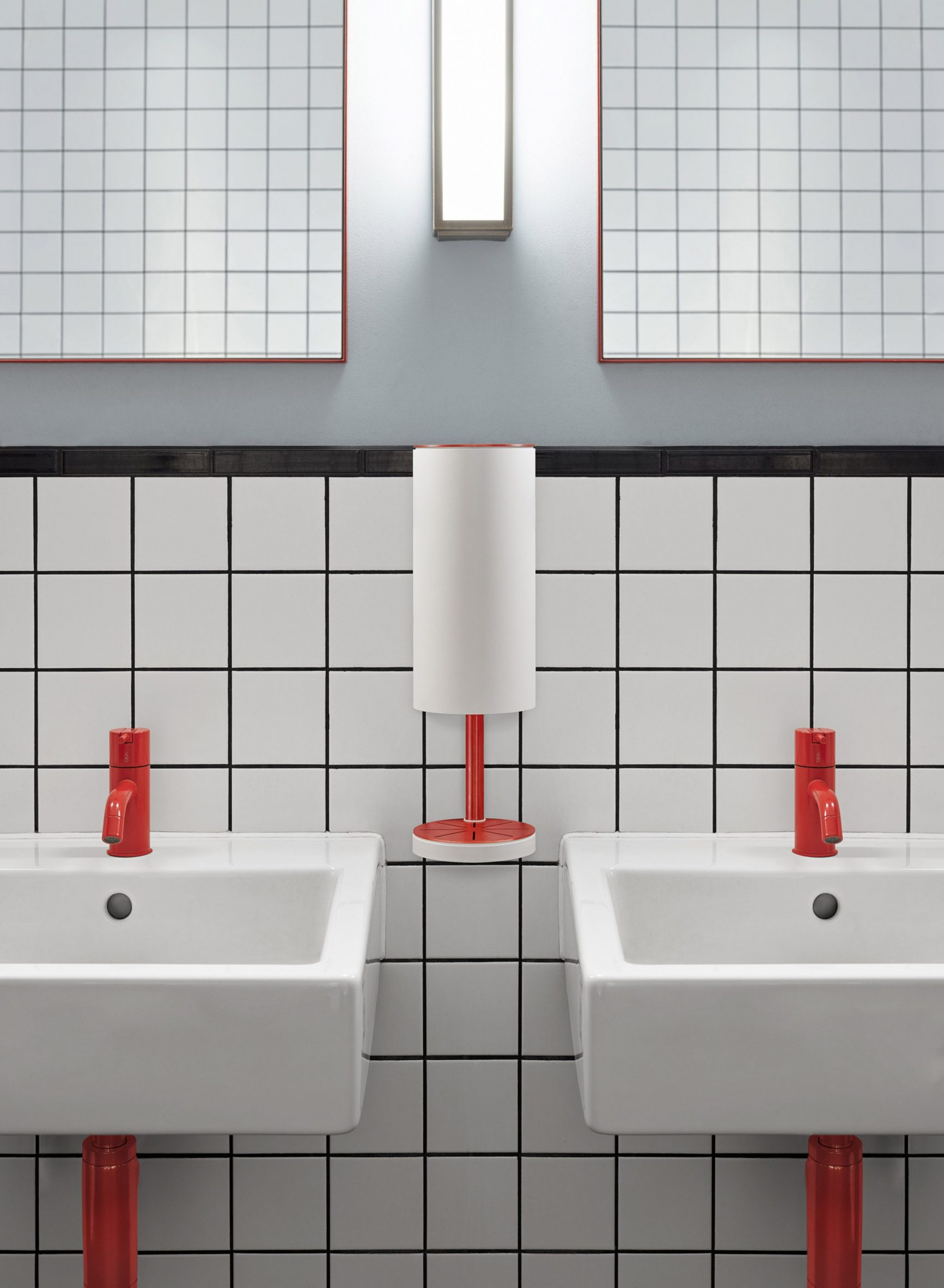 Red and white wall-mounted RS11 dispenser between basins in a public restroom
