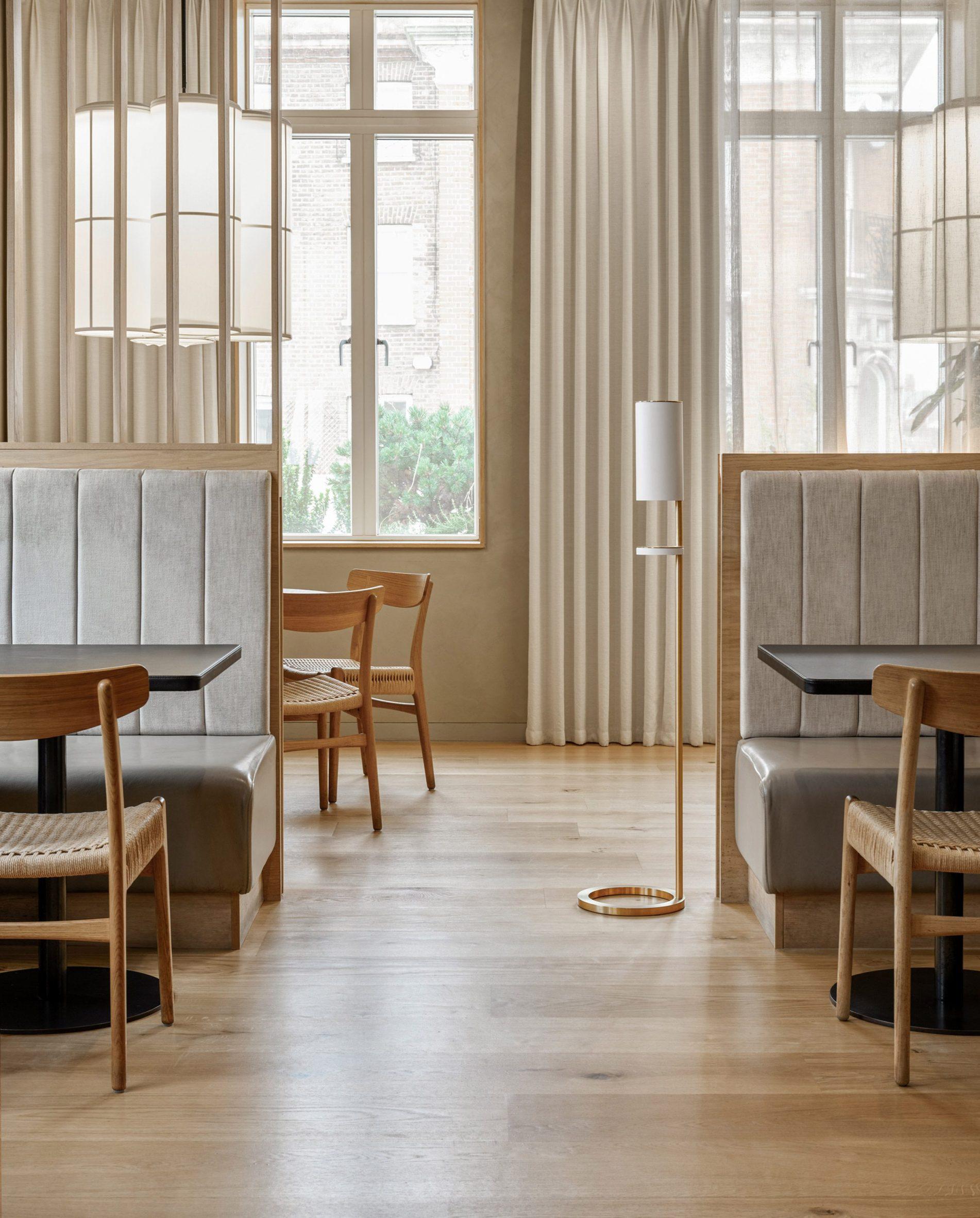 White freestanding hand sanitiser station in a light-filled contemporary restaurant