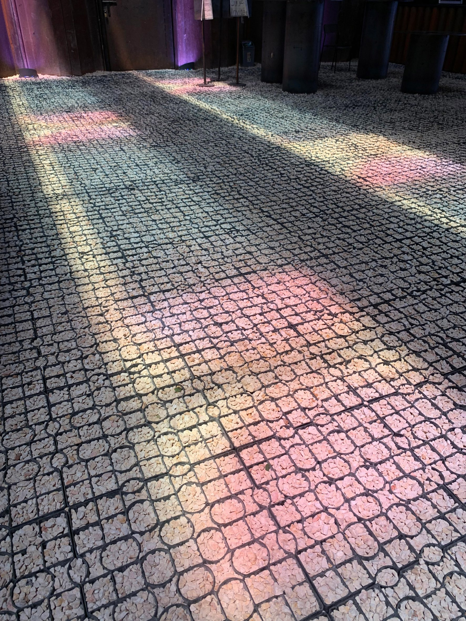 Pink, blue and yellow light on a pebble floor