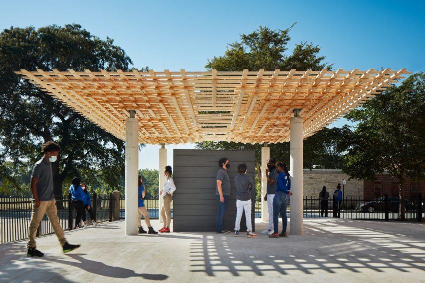 Студенты стоят под переплетенной деревянной крышей павильона СПЛАМ.
