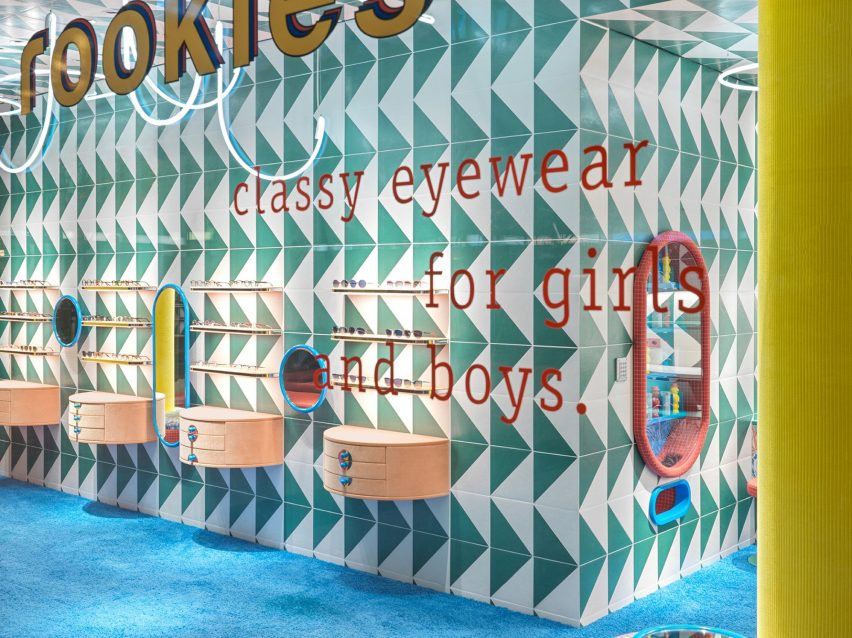 Brightly coloured tiles and carpet cover the walls and floor of the Leidmann eyewear store