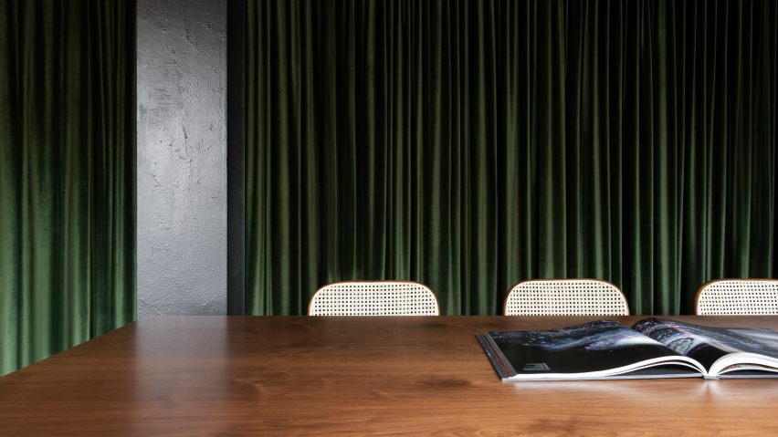 Detail image of dark wooden table and green curtain in office by Tala Fustok Studio