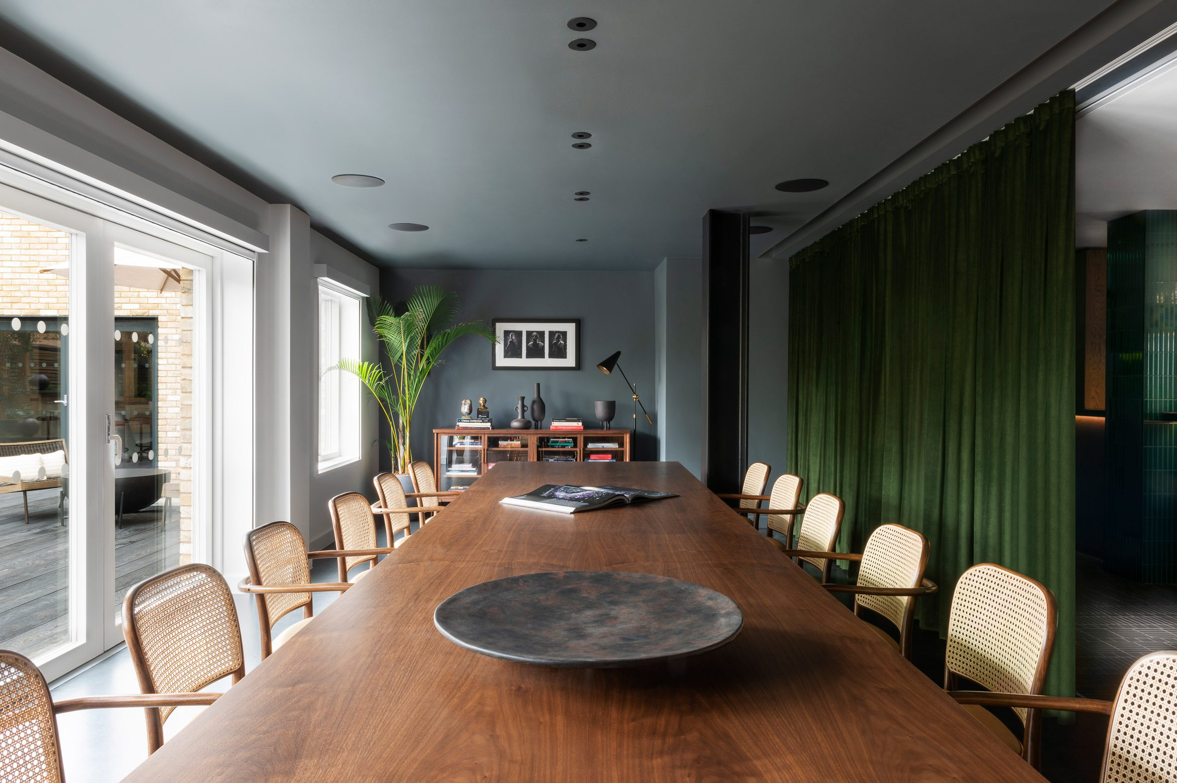 A large meeting table with rattan dining chairs