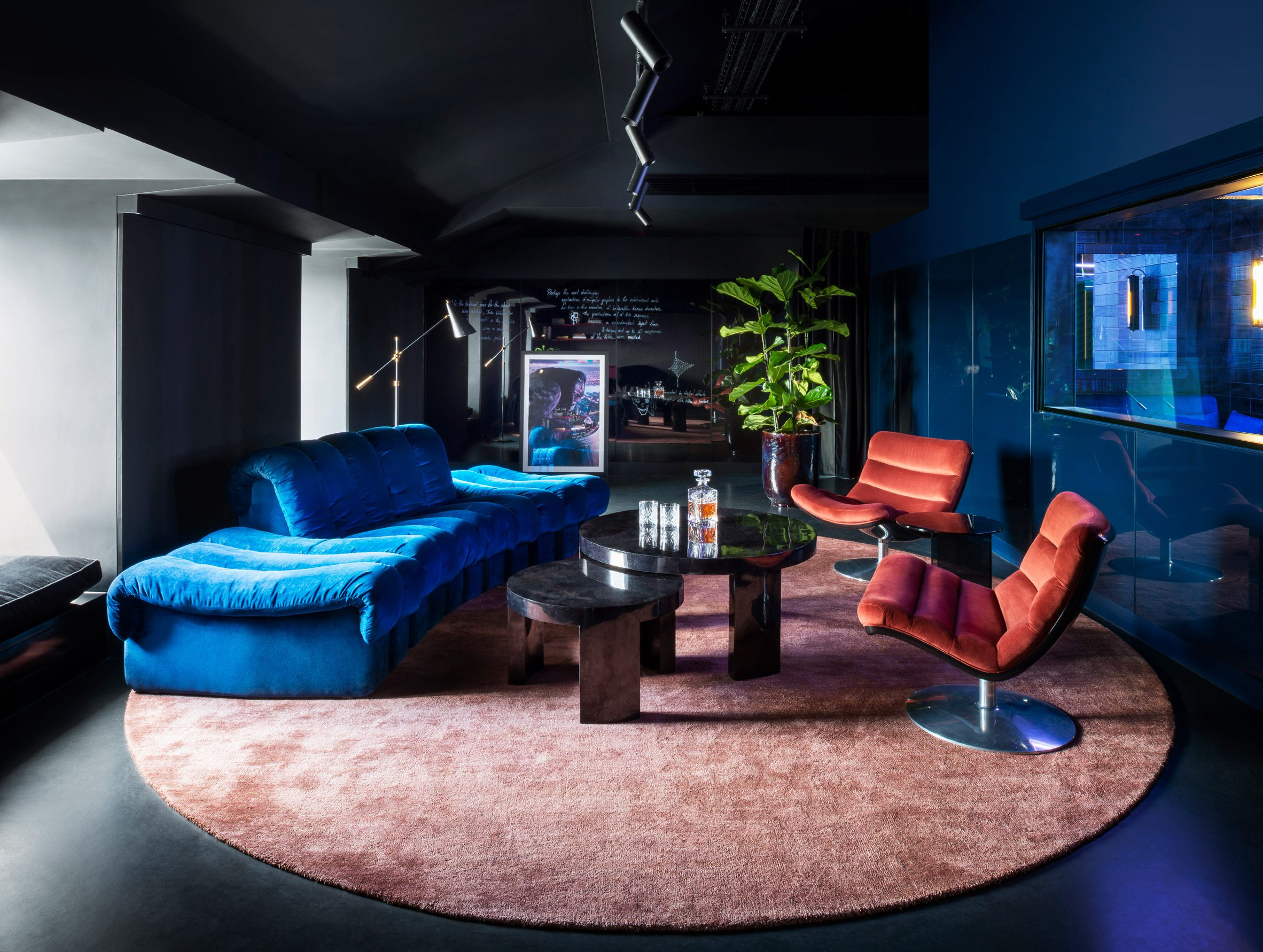 Blue and salmon furnishings pictured in a dark painted room