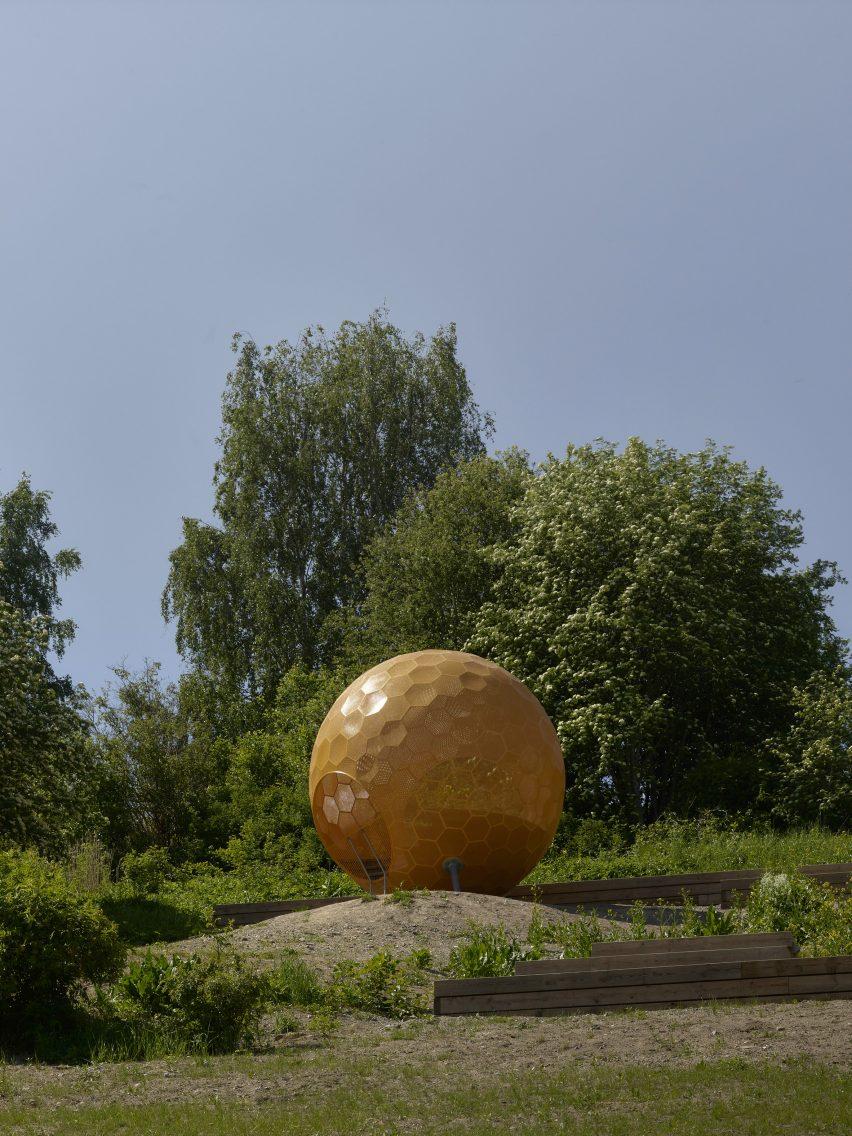 Перфорированная металлическая оранжевая сфера на вершине парка