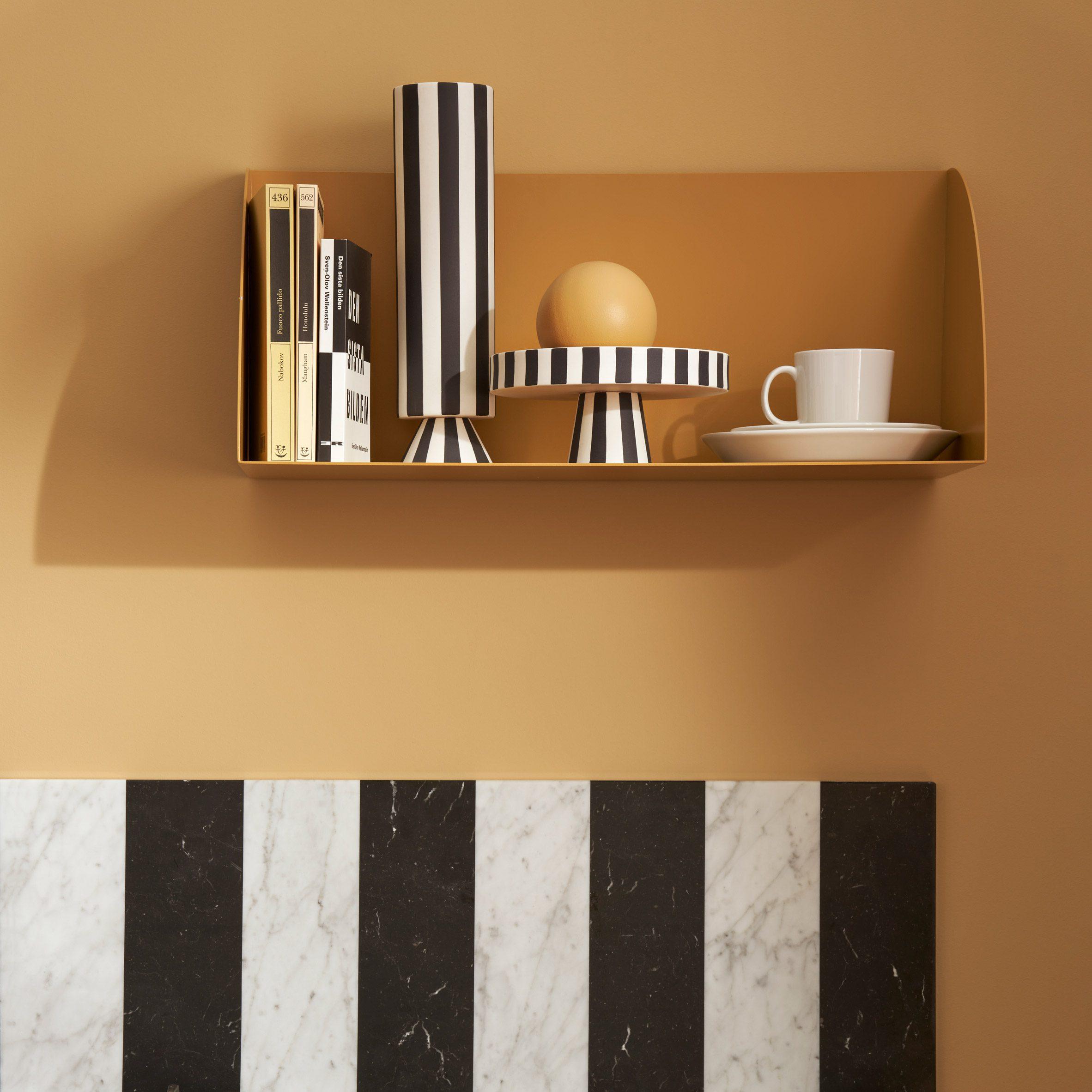 A yellow shelf above a marble countertop