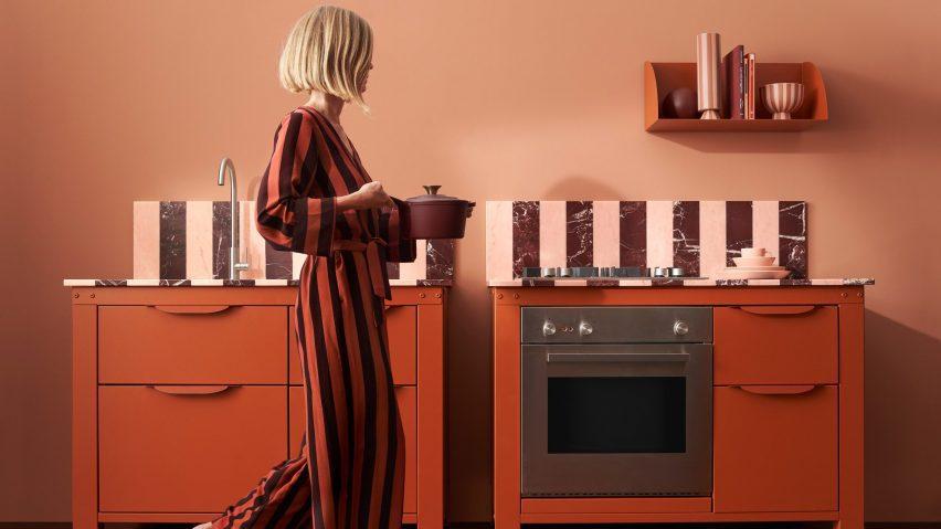 A woman walking through a red kitchen