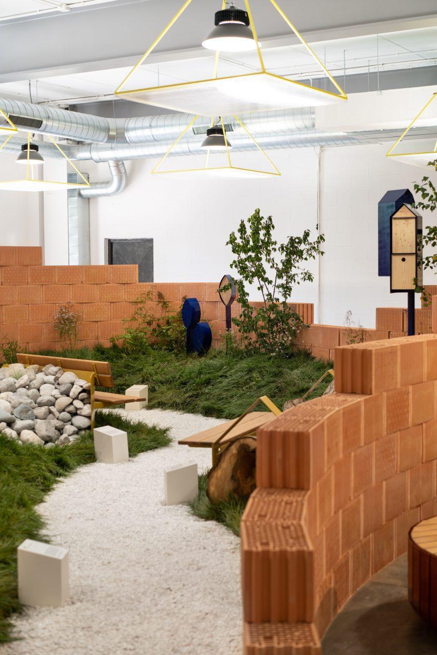 Инсталляция в закрытом парке от Note Design Studio с кирпичными стенами и каменным полом