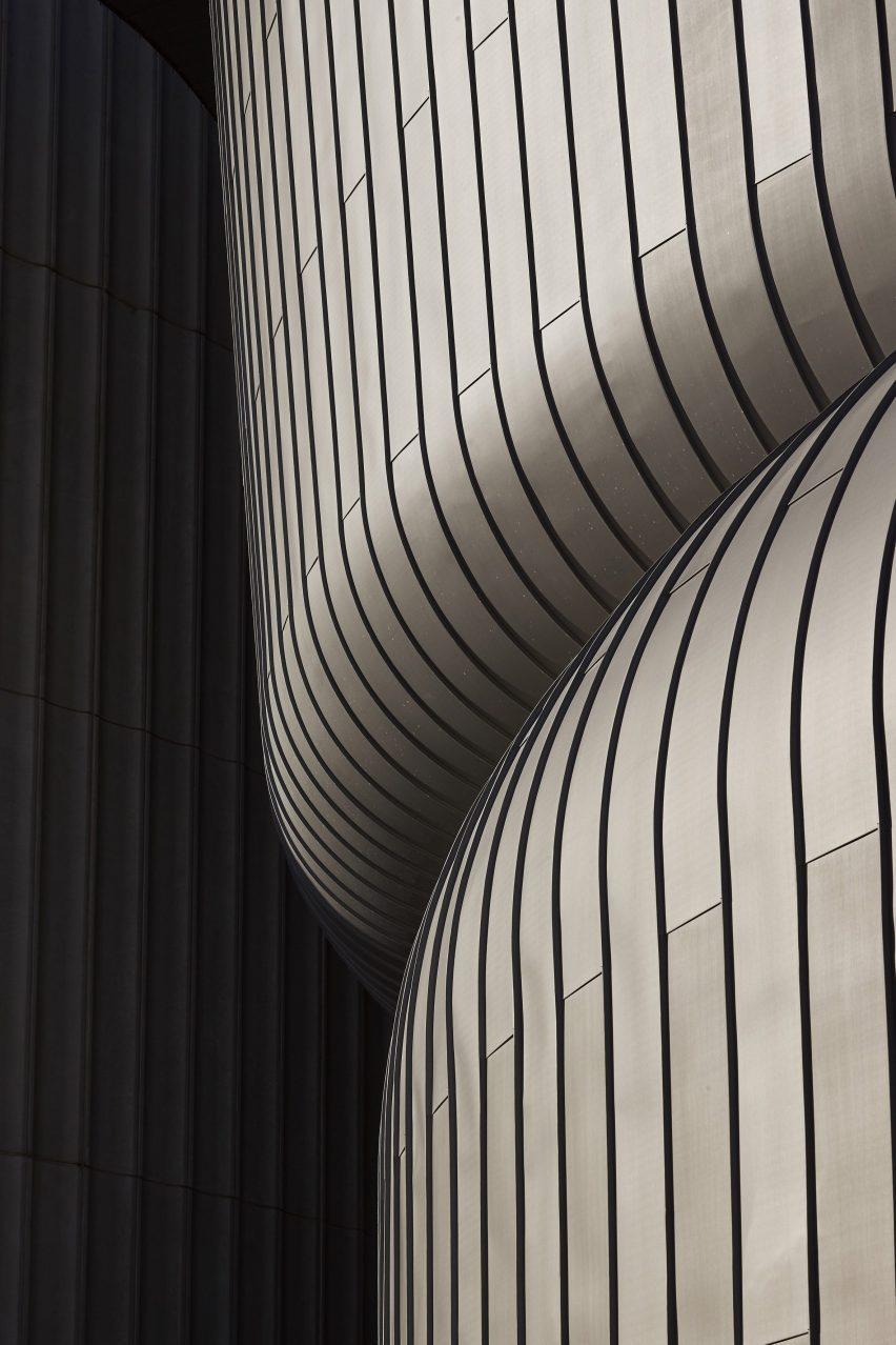 Цинковые панели изгибаются вокруг штабелированных объемов.