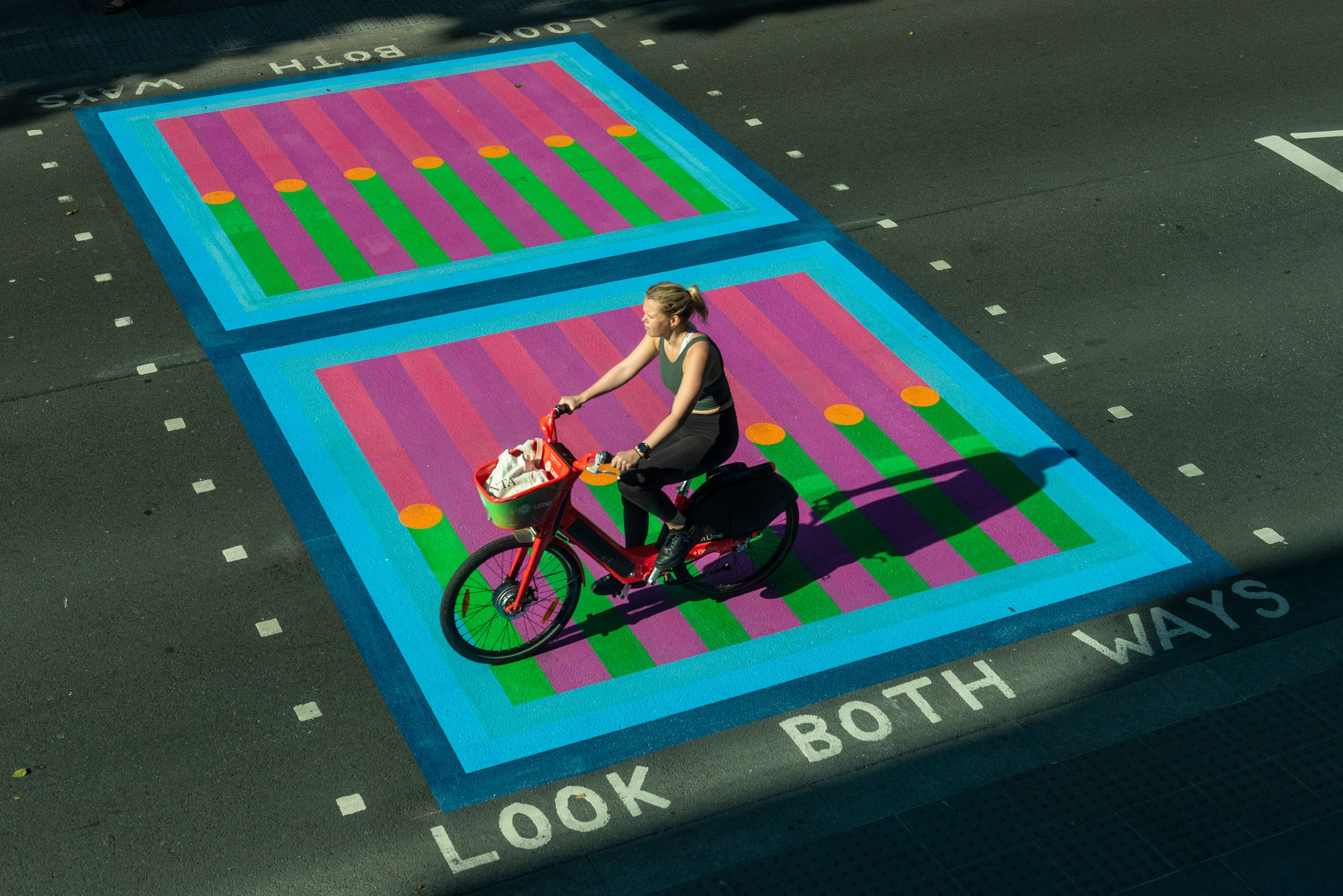 Cyclist riding over Yinka Ilori crossings for Bring London Together