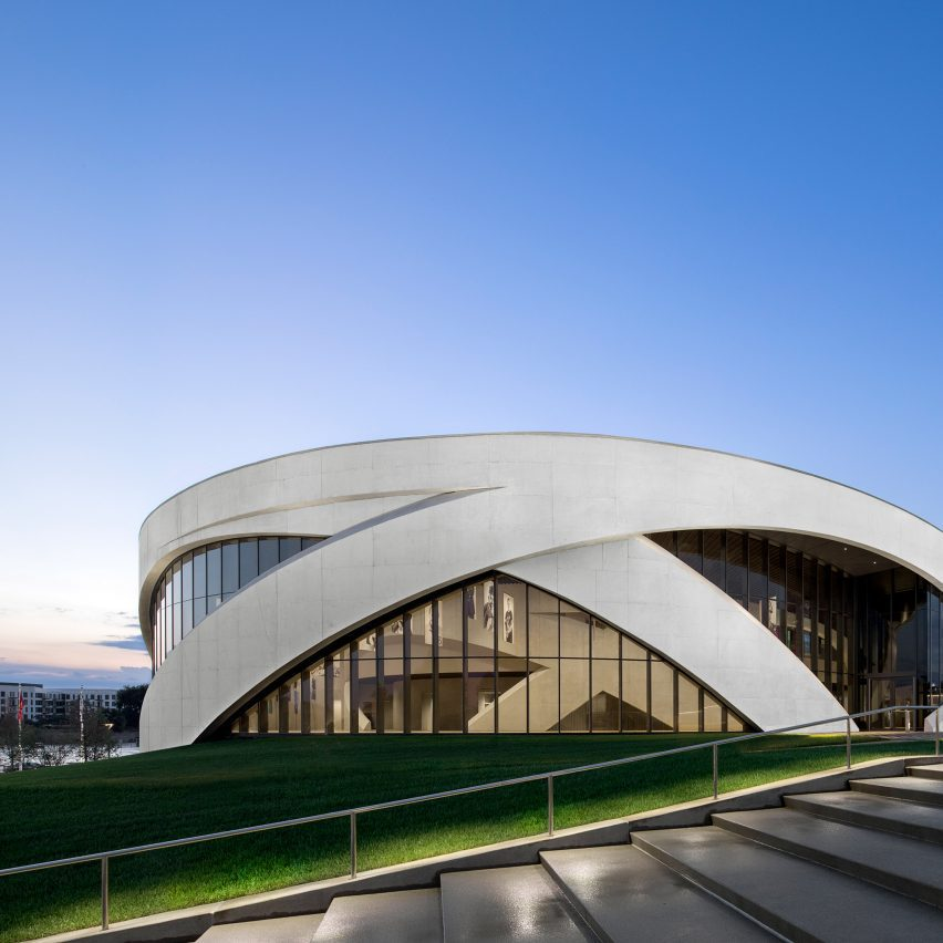 A large circular building with a glass facade and concrete arches enveloping the building