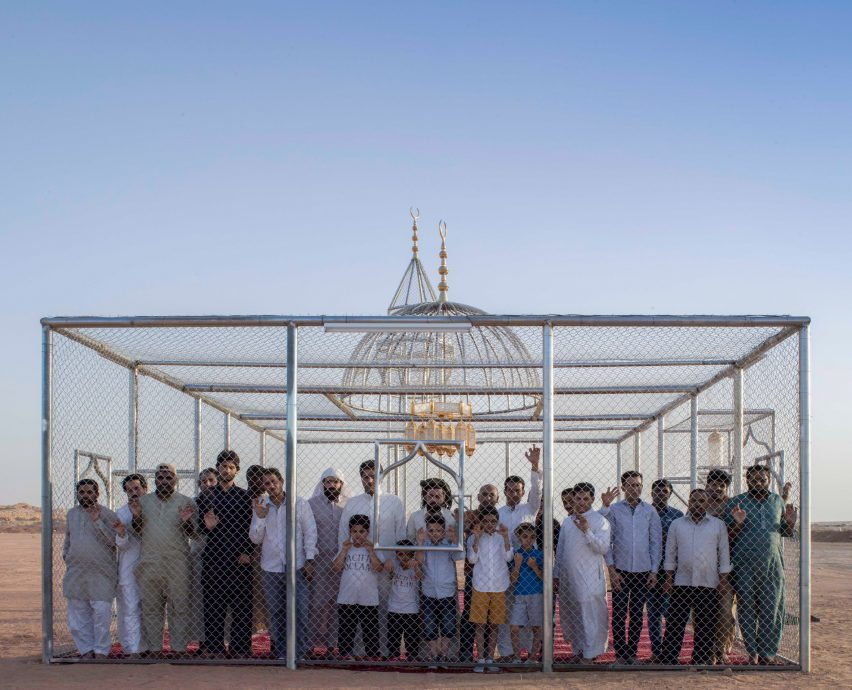 Толпа мужчин и детей выглядывает из-за заборов инсталляции «Рай имеет много ворот»