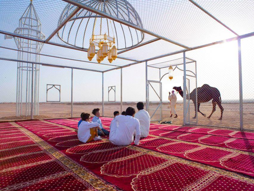 Группа людей сидит под куполом мечети из проволоки, глядя на проезжающего верблюда.
