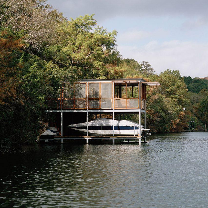 A two-storey boathouse jutting out onto a lake