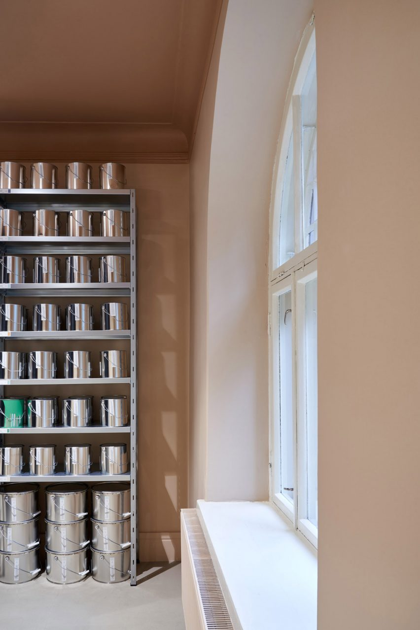 Shelves of paint tins in a pale pink room lit by a large arched window in Cover Story's shop