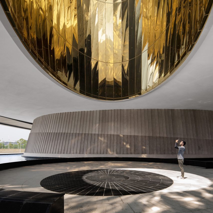 Figure standing under a reflective gold dome