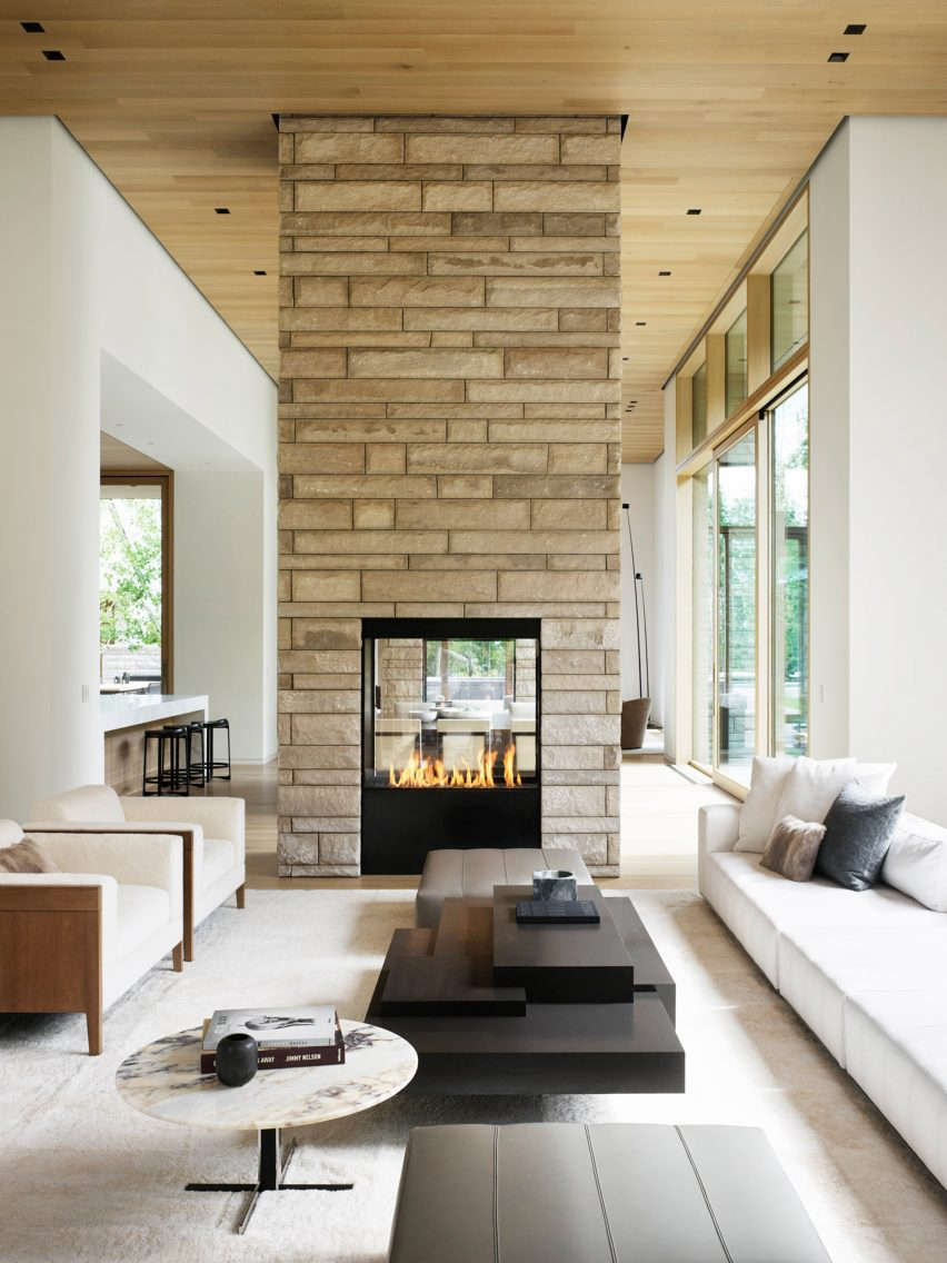 A stone wrapped chimney breast is located at the centre of a living room