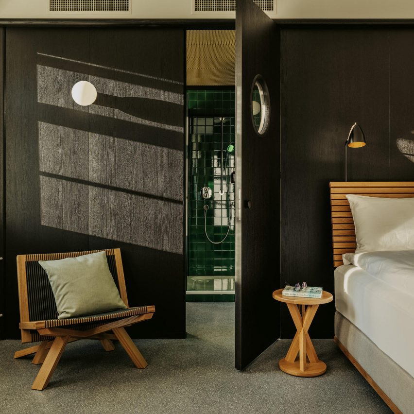 Bedroom with wooden furnishings looking into a green-tiled bathroom