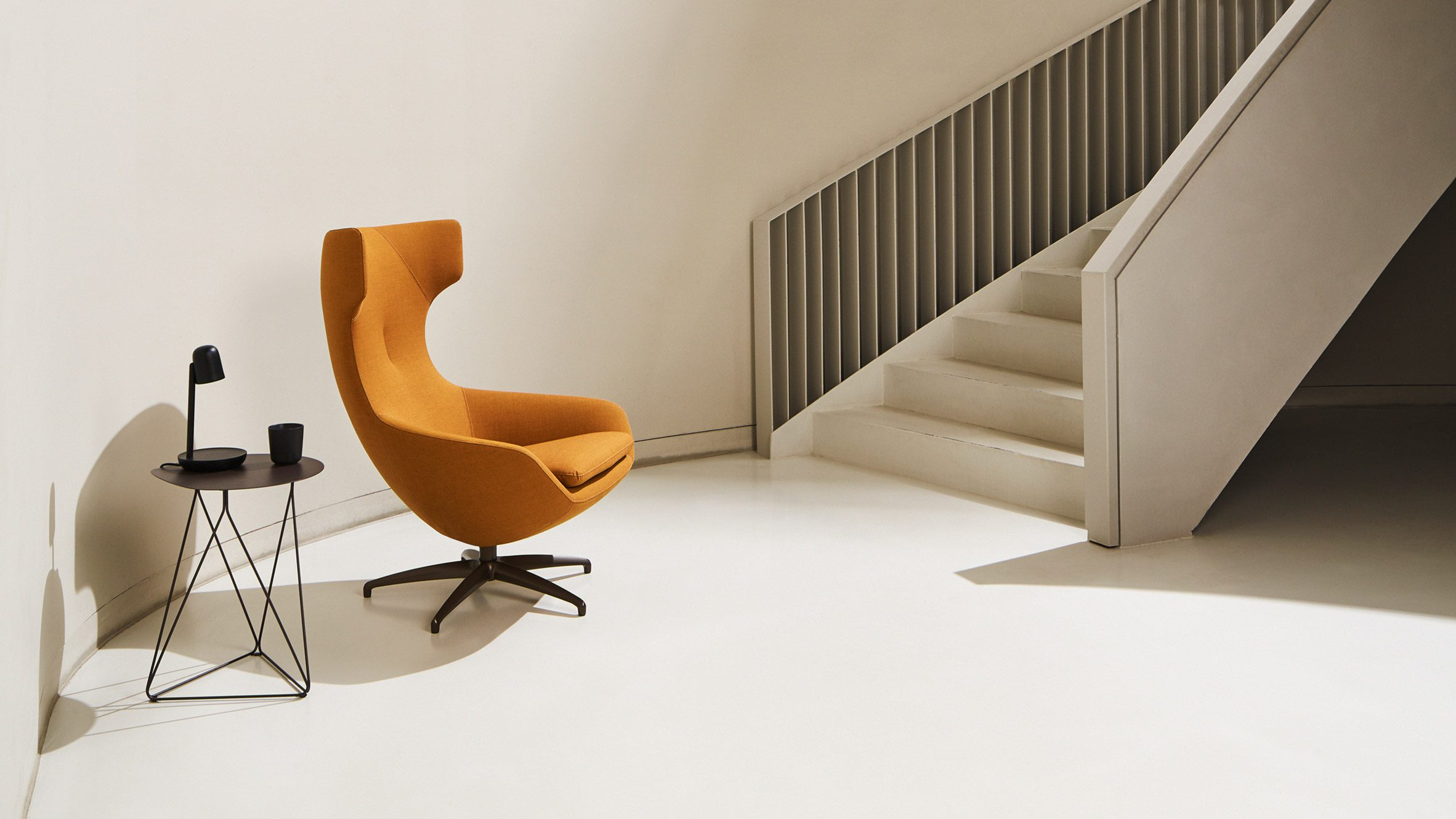 Bright orange LX662 armchair situated a neutral-coloured, pared-back room