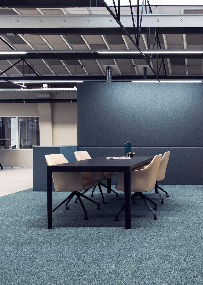 Empat kursi berlengan LXR671 berwarna krem mengelilingi meja hitam yang terletak di lingkungan kantor