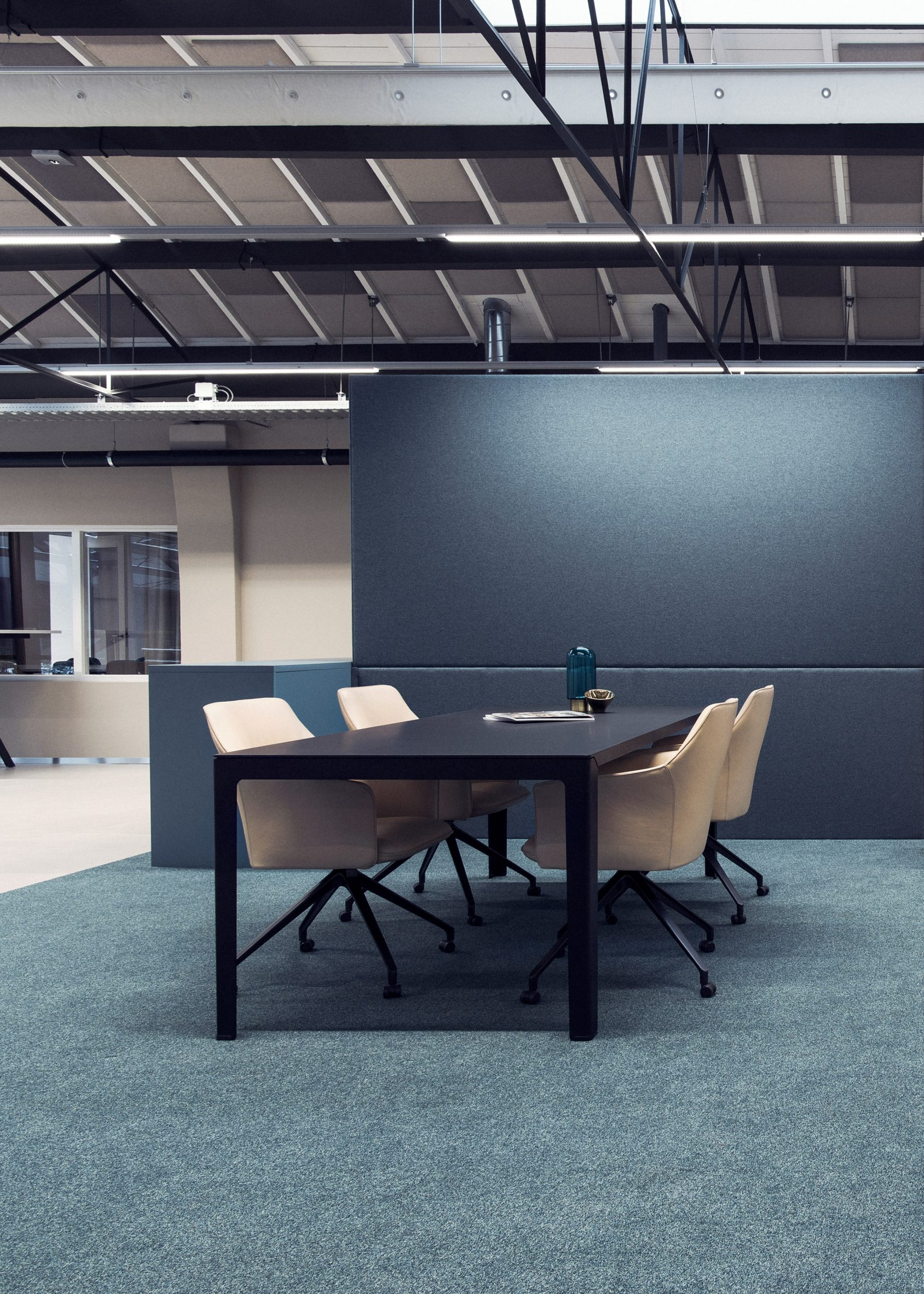 Four LXR671 armchairs in beige surrounding a black desk situated in an office setting