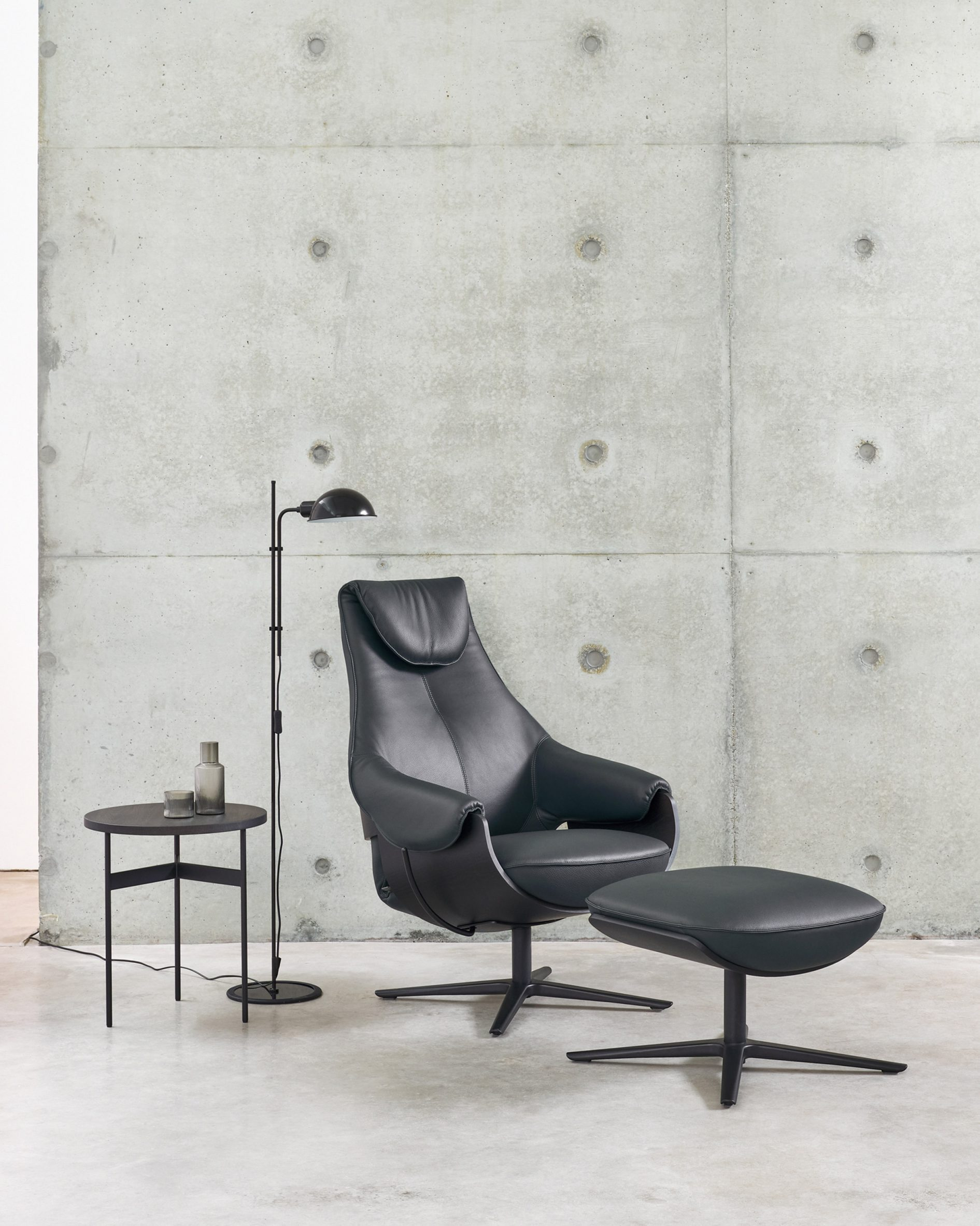 LXR10 armchair in a black leather finish with an accompanying footrest situated in a neutral-toned room