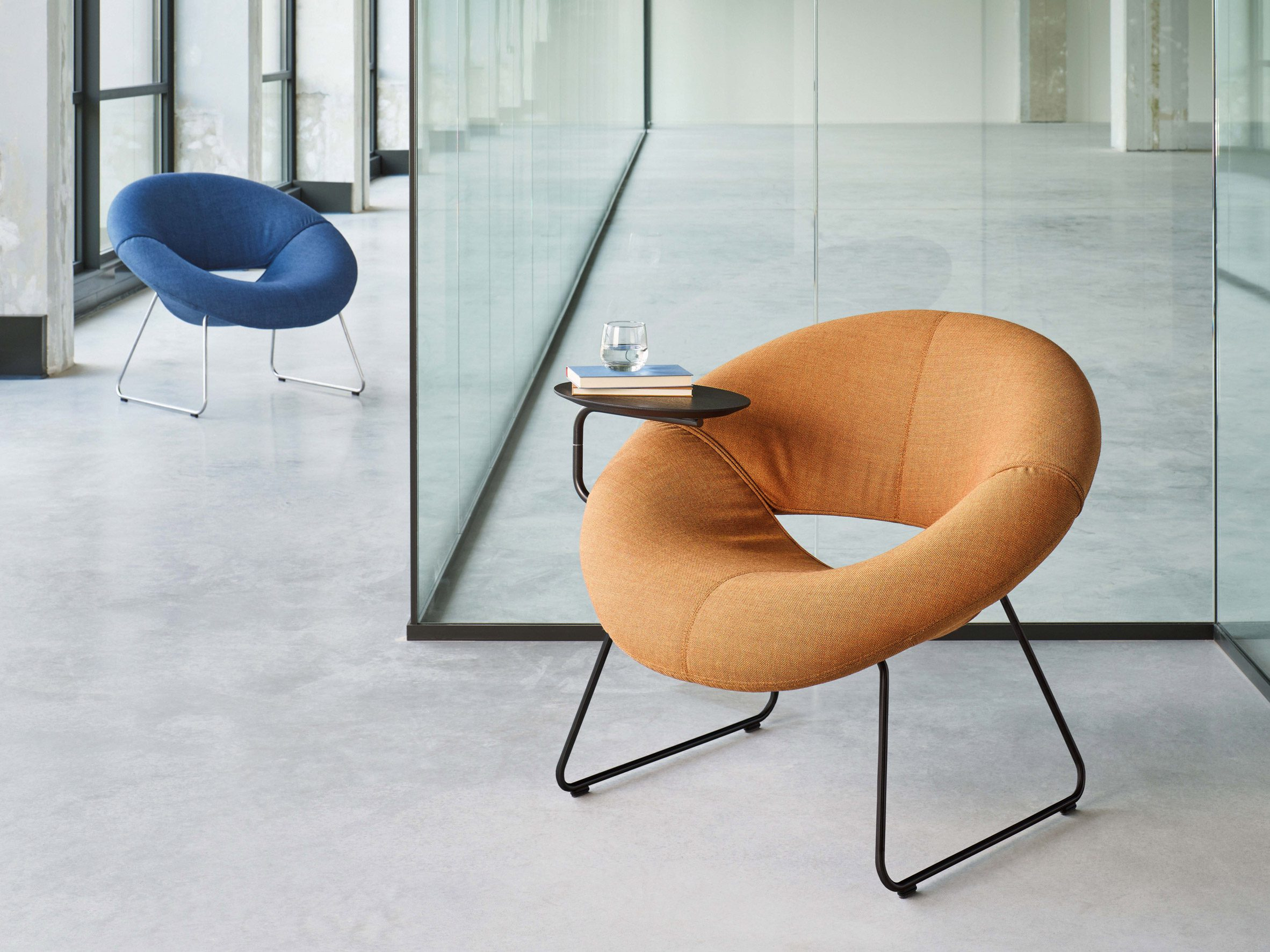 Orange LXR18 armchair with oak side table attached to its side holding books and water