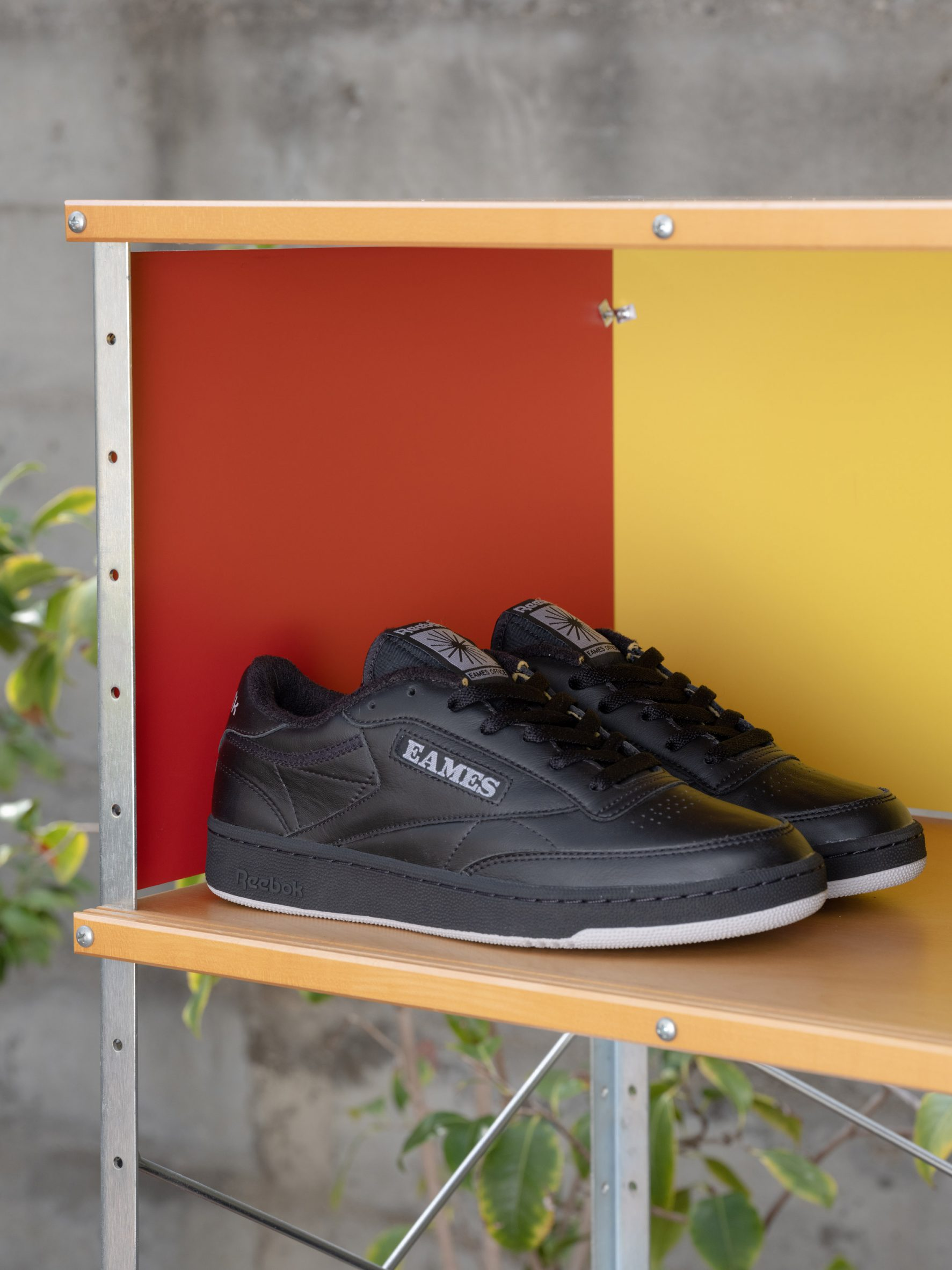 A pair of black Reebok trainers on a wooden shelf