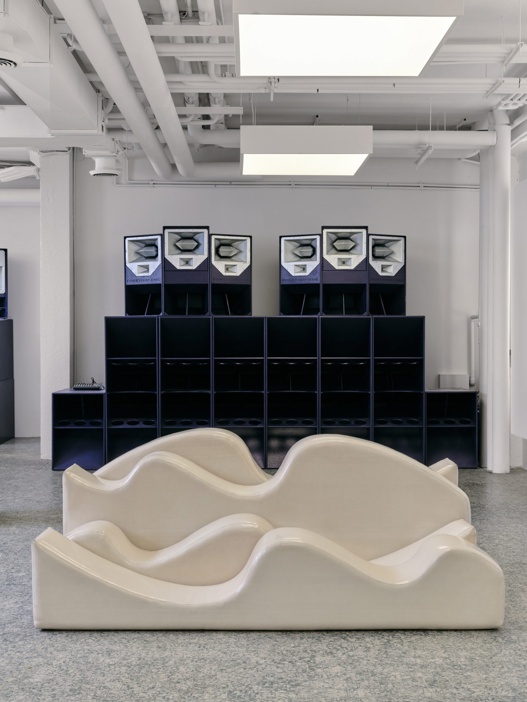 A wall of speakers occupies the rear of the showroom space