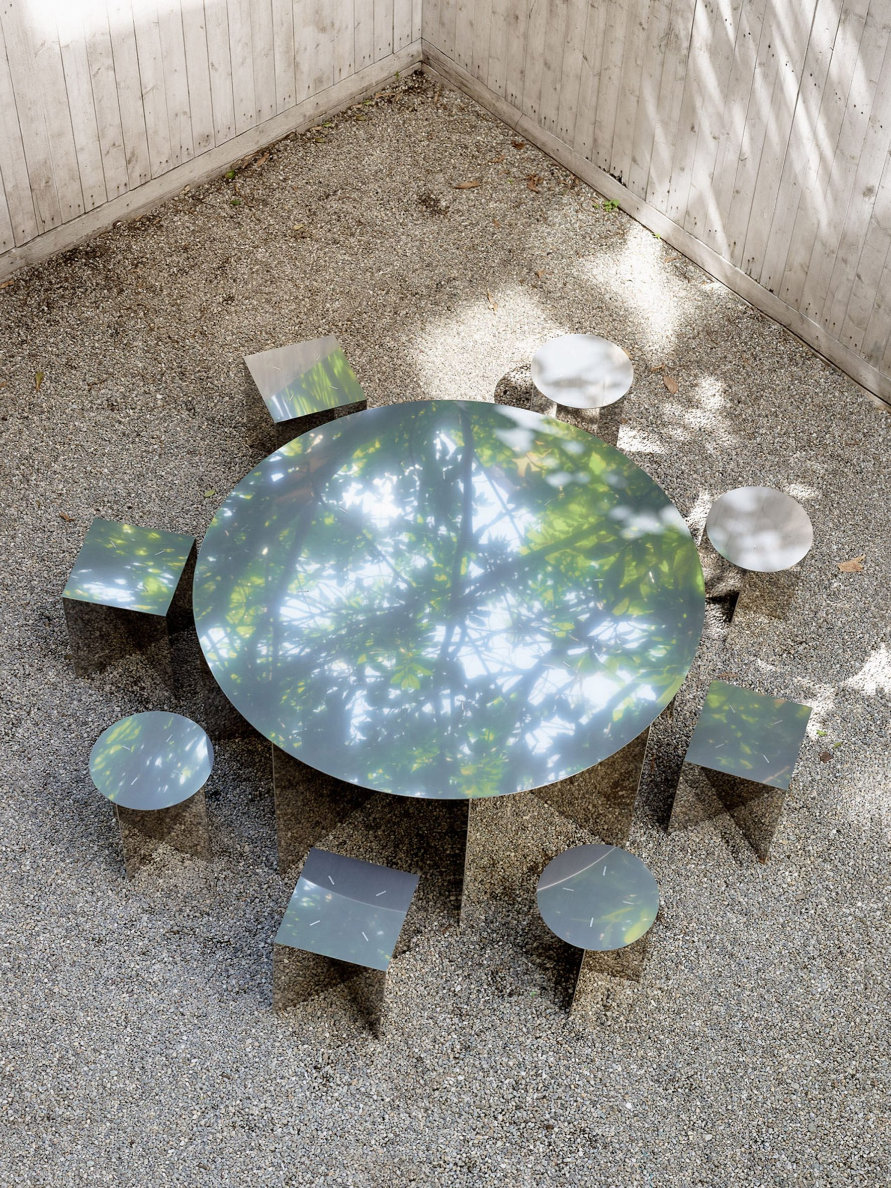 A metal table and chair reflects the trees and shrubbery
