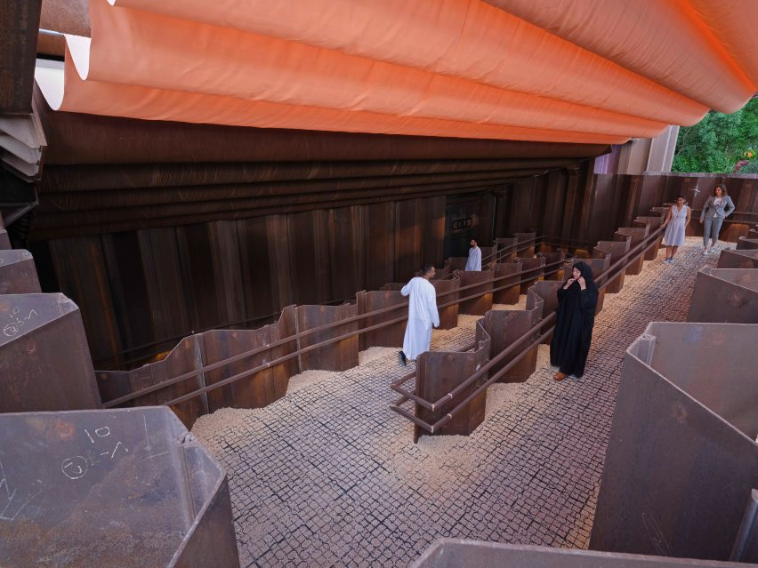 Visitors walk under an orange-coloured canopy at the Expo 2020 Dubai