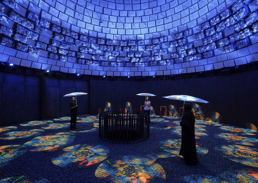 People with umbrellas stand in a dark, circular space with projections on the floor